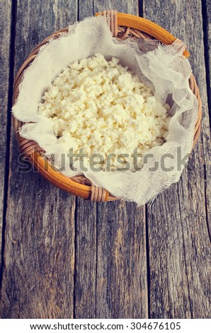 Cottage cheese in a wicker basket in rustic style