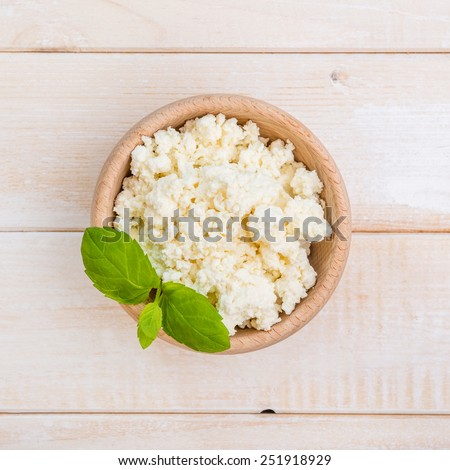 cottage cheese in a wooden bowl on a wooden background - stock photo