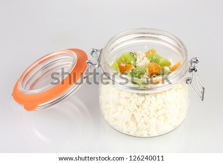 Cottage cheese in glass bottle with fruits, isolated on white