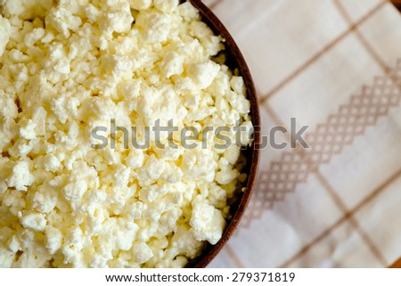 Cottage cheese in the wooden bowl on the napkin, top view