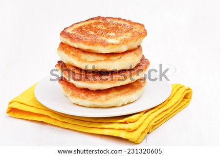 Cottage cheese pancakes on white plate - stock photo