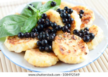 Cottage cheese pancakes with blackcurrant, closeup - stock photo