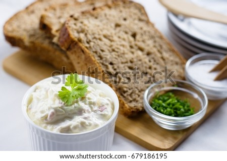 Cottage cheese spread in a ceramic bowl served with slices of wholegrain bread slices