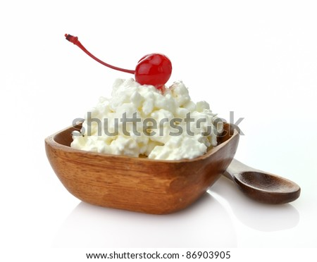 Cottage cheese with cherry in a wooden bowl - stock photo