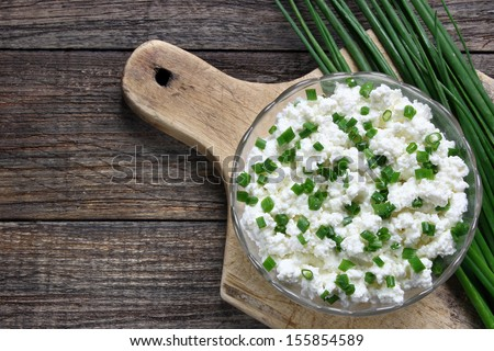 Cottage cheese with chives in glass bowl  - stock photo