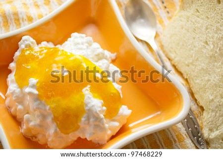 cottage cheese with jam in the orange bowl - stock photo