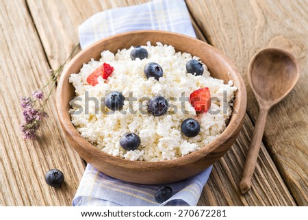Cottage cheese with ripe blueberries in a wooden plate - stock photo