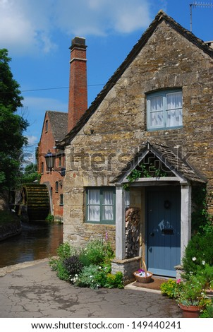 Cottage in front of a mill in the picturesque Cotswolds town of Lower Slaughter in England - stock photo