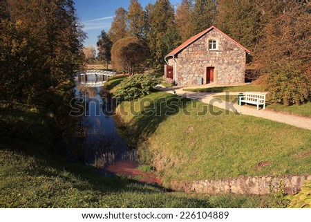 Cottage in the autumn park - stock photo