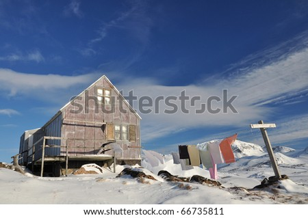 Cottage in the Kulusuk village and clothes horse, Greenland - stock photo