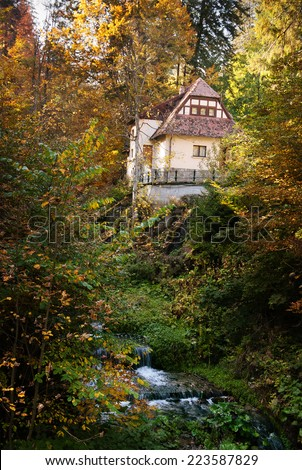 cottage in the woods near a creek - stock photo