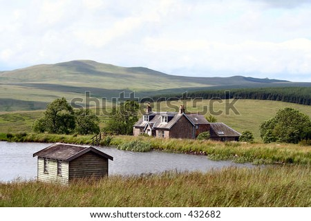 Cottage, lake and boathouse in the Scottish Borders, UK - stock photo