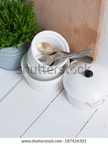 Cottage life, country kitchen decoration: a house plant in a metal pot, kitchen pottery, utensils and napkins on white painted board. Cozy home country life background is.
