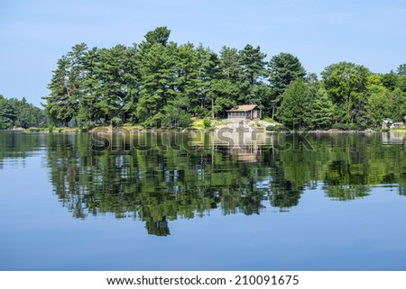 Cottage on a Tranquil Lake - stock photo