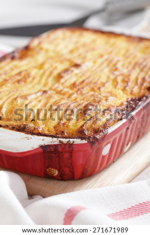 Cottage pie in a red baking dish - stock photo