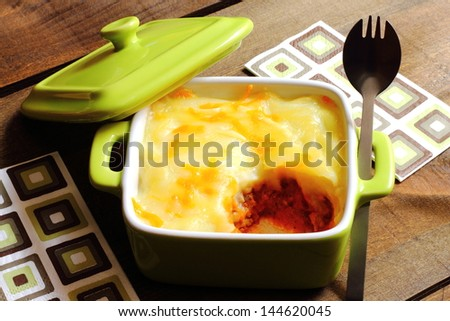 Cottage pie served in a green casserole - stock photo