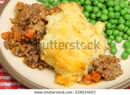 Cottage pie served with garden peas. - stock photo