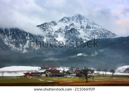 Cottages and snowy peak. The 'Hochstaufen' is located in the north of 'Bad Reichenhall' and is the part of Alps. The mountain belongs to the 'Staufen' massif. - stock photo