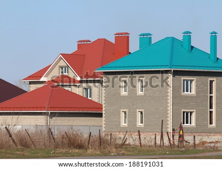 Cottages with red and blue roofs against a blue sky - stock photo