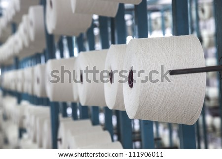 cotton cone hang on racks and the cotton threads coming from these reels and combined together - stock photo