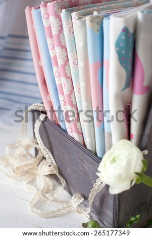 Cotton fabrics bundle in a wooden box. Home sewing and handmade hobbies concept. - stock photo