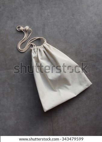 Cotton laundry bag on cement floor background - stock photo