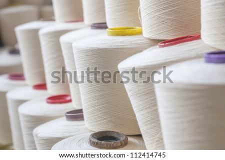 cotton threads cone stacked together in a factory - stock photo