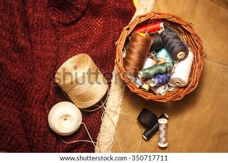 Cotton threads for sewing and needles in a woven basket on a wool sweater and leather cloth - stock photo