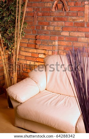 Couch at corner of brick's wall with yelow light of lamp - stock photo
