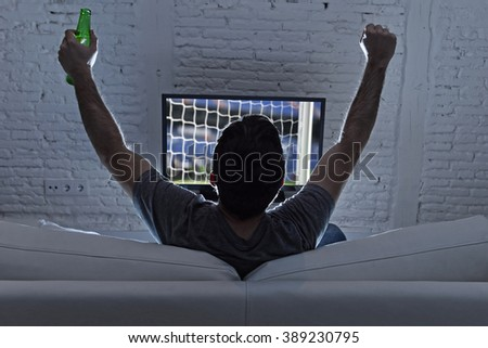 couch back view with young man home alone watching soccer or football game in television enjoying and celebrating goal and victory holding beer bottle gesturing on the sofa happy and excited - stock photo