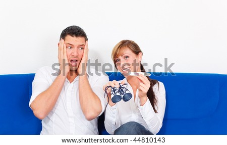 Couch sitting couple with positive pregnant test while man is very surprised and shocked , is female happy looking in camera - stock photo