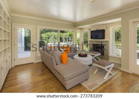 Couch with fireplace in glass house open floor plan. - stock photo