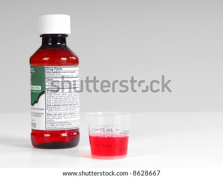 Cough medicine bottle and warning label with poured dose on counter - stock photo
