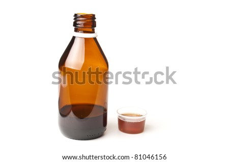 Cough medicine in a glass bottle with dosage cup filled - stock photo