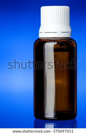 Cough syrup, glass bottle with a white plastic cover on glass with a blue background, nobody. - stock photo