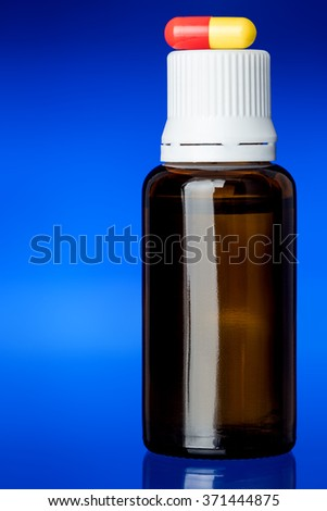 Cough syrup, glass bottle with a yellow-red pill on a cover on glass with a blue background, nobody. - stock photo