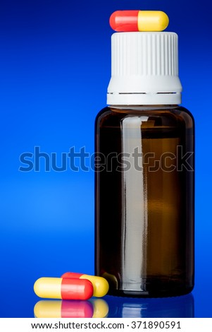 Cough syrup, glass bottle with a yellow-red pill on glass with a blue background, nobody. - stock photo