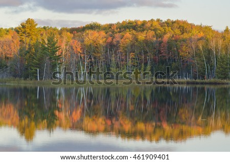 Council Lake reflects the far shore autumnal colors on a morning with an approaching storm, Hiawatha National Forest, Alger County, Michigan