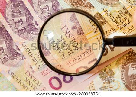 Counterfeit money concept. Polish zloty banknotes currency and magnifying glass - stock photo