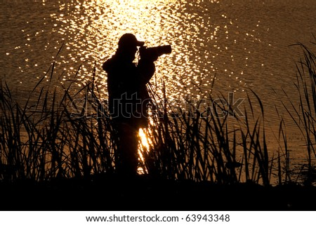 Countre jour silhouette of a photographer in the sunset reflection on water. - stock photo