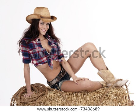 Country Afternoon Goes Faster Beautiful Cowgirl Taking Break on Hay-bale Western Woman - stock photo