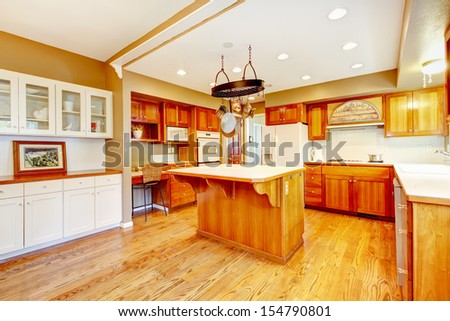 Country American farm house kitchen with fall views. Large room with hardwood floor, kitchen island and breakfast area. - stock photo