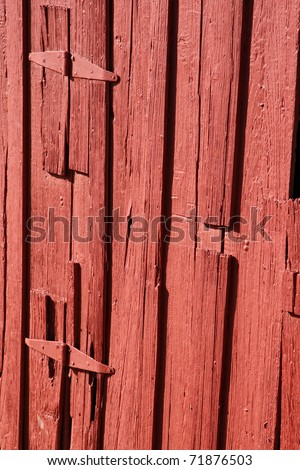 Country and agricultural-themed image of the side of an authentic old red barn in the American West.
