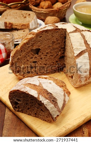 Country bread on the wooden cutting board     - stock photo