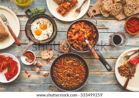 Country dinner tabletop with slow cooked meal in three skillets. Organic , homemade, healthy meal concept. Rustic style from above . Vegetables stew, boiled sausages lentils, fried eggs.  - stock photo
