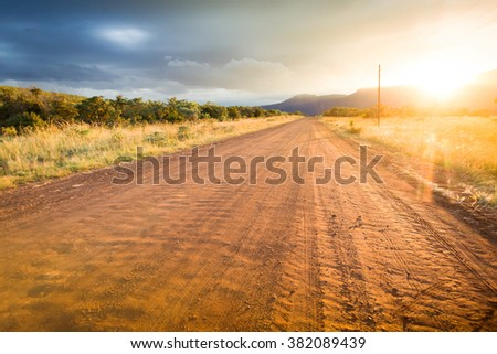 Country dirt road heading in South Africa outside safari and game reserve during sunrise - stock photo