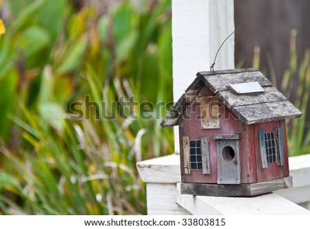 Country folk style bird house on front porch railing - stock photo