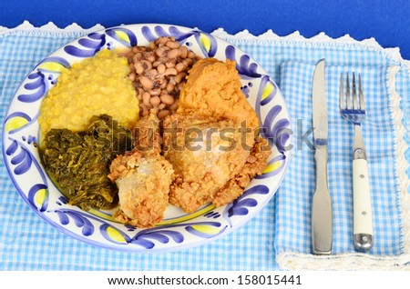 Country fried chicken dinner with collard greens; creamed corn; black eyed peas; and candied yams on blue plate against blue gingham. - stock photo