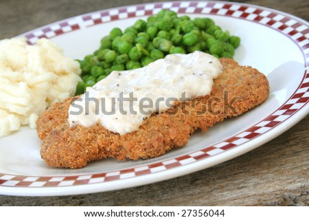 Country fried steak with gravy and side dishes of mashed potatoes and fresh peas.