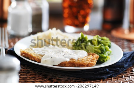 country fried steak with southern style peppered milk gravy shot in panorama style - stock photo
